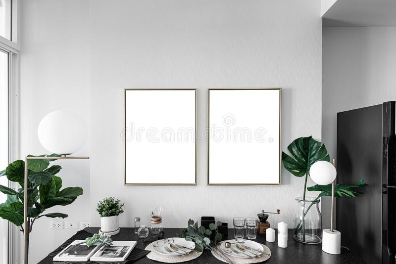Cozy dining corner with nice decoration in scandinavian style with empty golden frame install on the wall / interior design decora stock photo