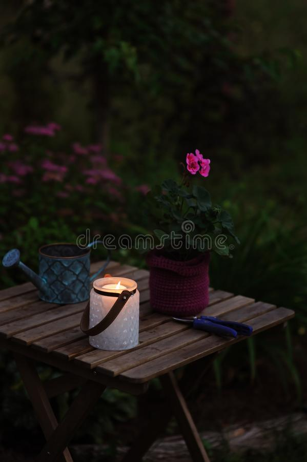 Cozy evening garden summer scene with candle light. Geranium flower in pot and vintage watering can stock image
