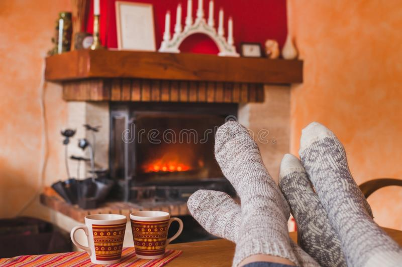 Cozy family evening at home near fireplace in winter. Feet of couple in socks and two cups of tea, weekend stock photography