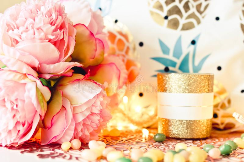 Cozy female composition with flowers candle and lights. Sweet interior decor. Ceramic candle with bouquet of pink flowers and candles on a wooden table or shelf royalty free stock photo