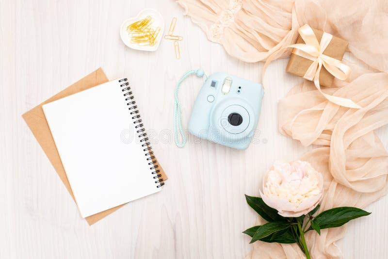 Cozy feminine home office desk. Modern instant camera, beige scarf, peonies flowers, paper notepad. Top view, tender minimal flat stock photos