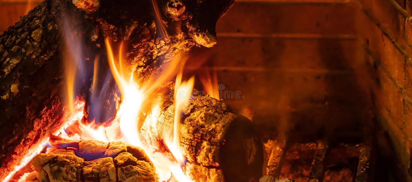 Cozy fireplace. Wood logs burning, relaxation and warm home royalty free stock image