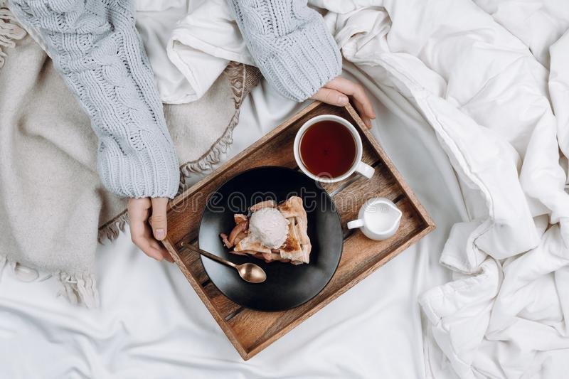 Cozy flatlay of bed with wooden tray with pie, ice cream and black tea and woman`s hands stock photo