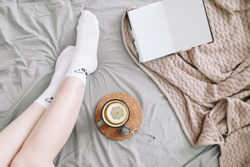Cozy flatlay of woman legs in bed with a book and a cup of lemon tea. Cozy morning at home. stock photo