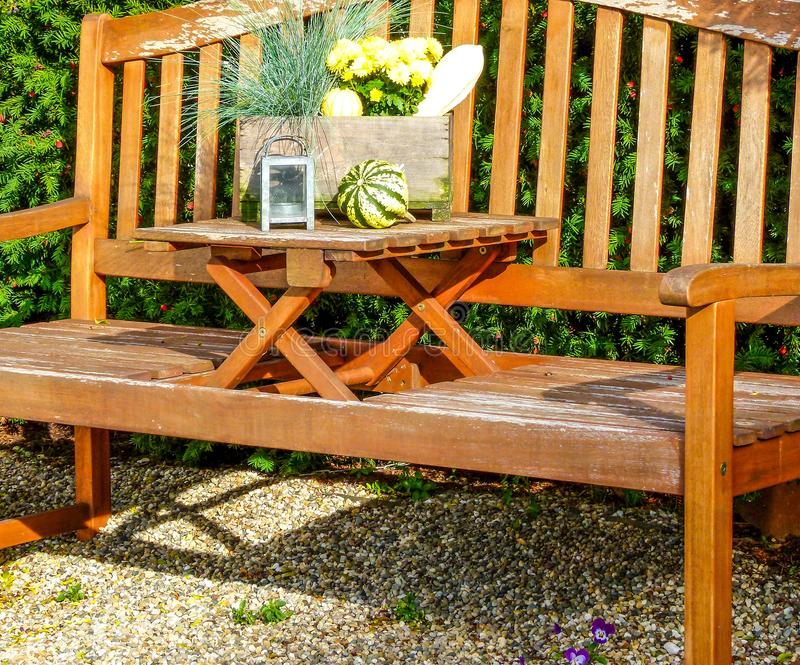 Cozy garden bench with recliner and flip-up table royalty free stock photography