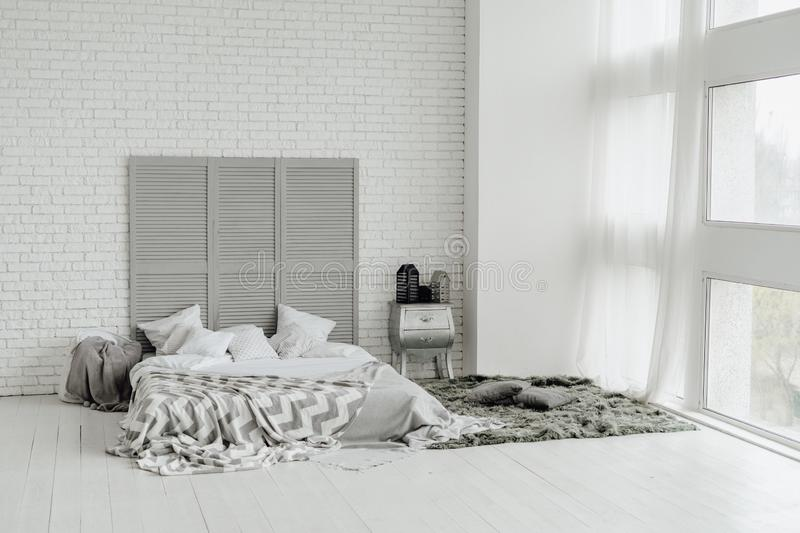Cozy Grey Bedroom Interior Large Window Design. White Modern Decor for Messy Bed Space in Scandinavian Estate Floor. Minimal Loft Style Living Double Bedside stock photo