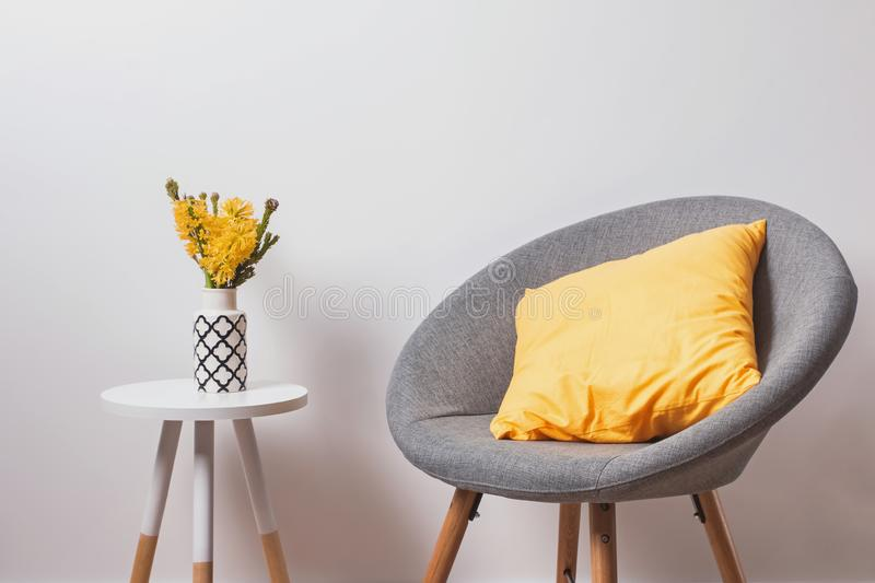 Cozy grey chair with yekllow pillow and flowers in the vase standing near the white wall. royalty free stock images