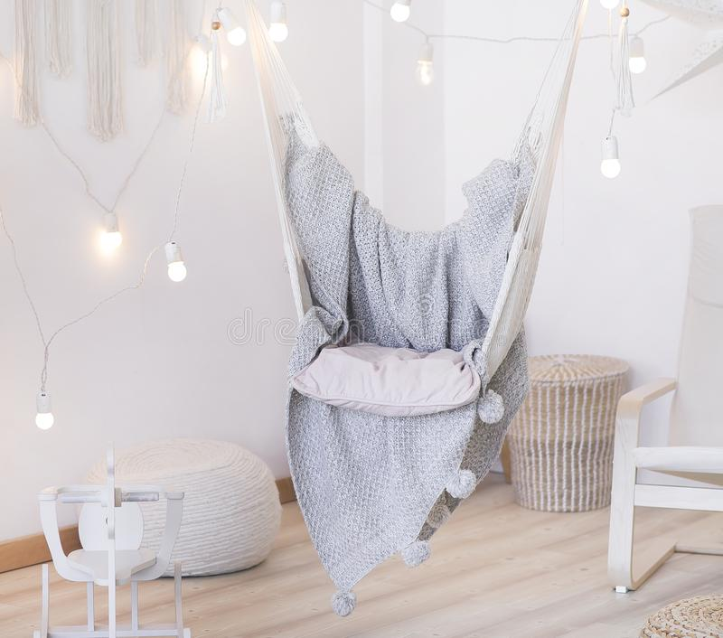 Cozy hammock chair in a bright room. Pastel colors. Gray bedspread. A garland of light bulbs royalty free stock photography