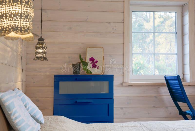 Cozy heldere slaapkamer in een houten huis in Scandinavische stijl met decoratieve bloemen in potten Kleurjaar 2020, klassiek stock afbeelding
