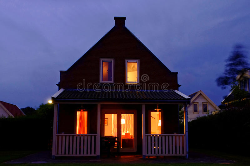 Cozy holiday home with veranda lighted by night royalty free stock photography