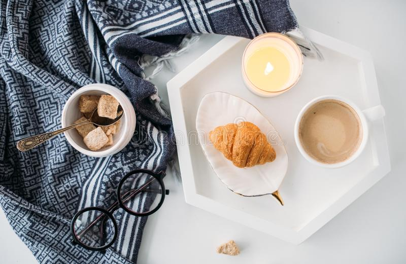 Cozy home breakfast, warm blanket, coffee and croissant on white. Tray, hipster styled flat lay stock photography