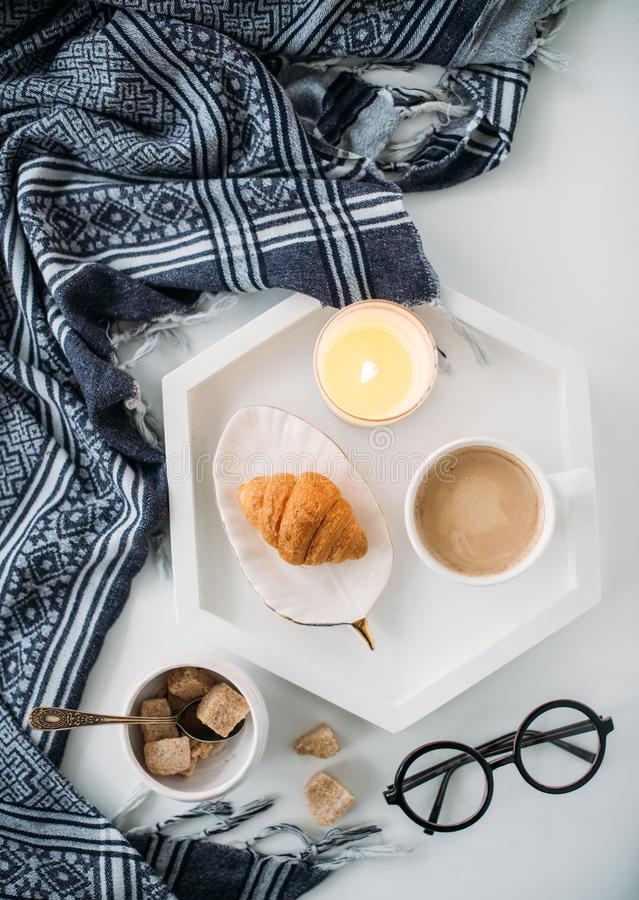 Cozy home breakfast, warm blanket, coffee and croissant on white. Tray, hipster styled flat lay stock images
