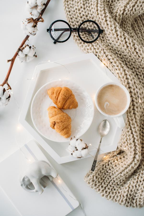 Cozy home breakfast, warm blanket, coffee and croissant on white. Tray, hipster styled flat lay royalty free stock image