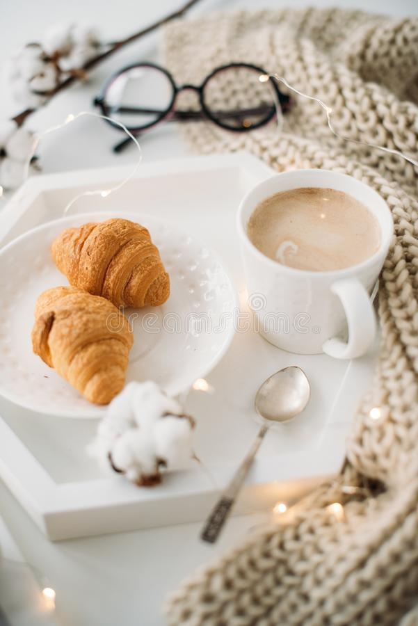 Cozy home breakfast, warm blanket, coffee and croissant on white. Tray, hipster styled flat lay royalty free stock images