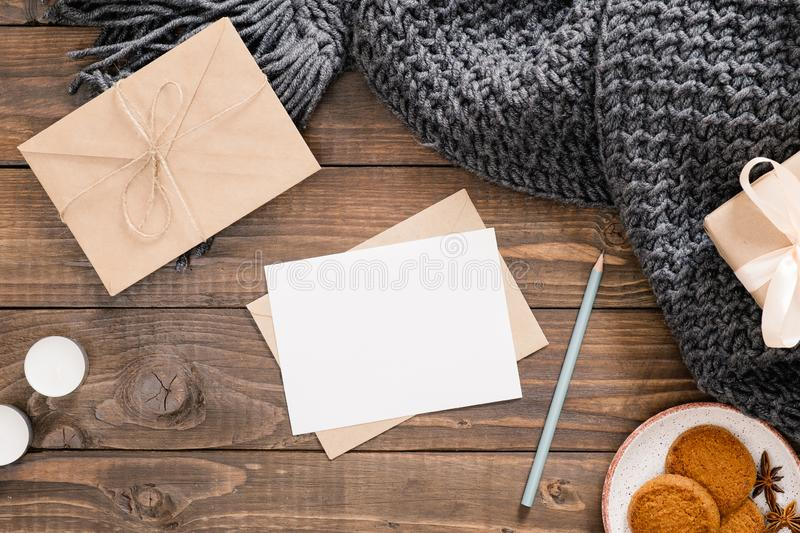 Cozy home desk, hygge, autumn fall concept. Blank paper card mockup, craft envelope, cookies, candles, women fashion scarf, gift. Box on wooden background. Flat royalty free stock photo