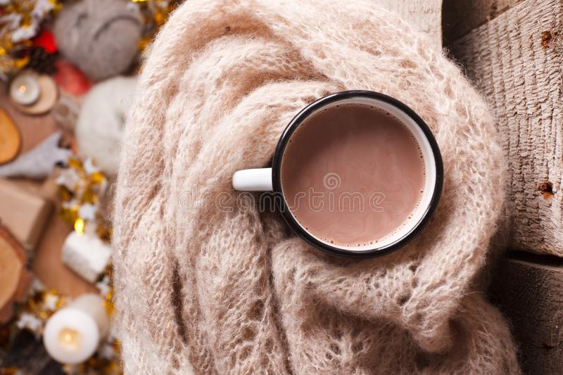 Cozy home details, winter season, hygge concept - cup of cocoa and woolen scarf on wooden, mindfullness and relax background.  royalty free stock images