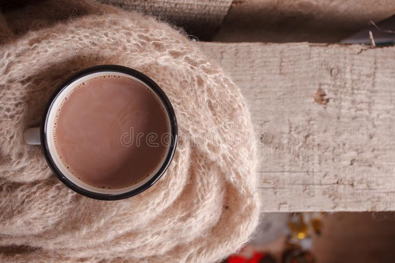 Cozy home details, winter season, hygge concept - cup of cocoa and woolen scarf on wooden, mindfullness and relax background.  stock image