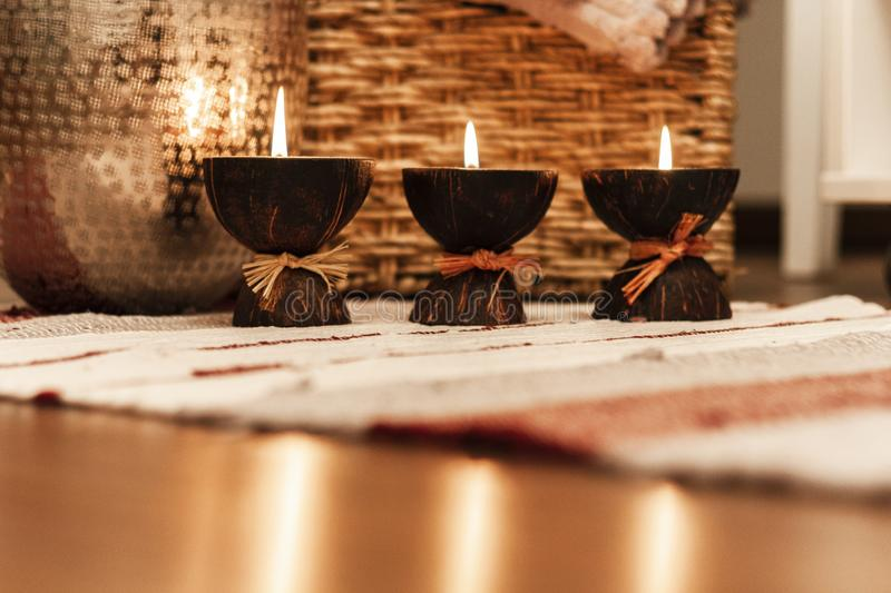 Cozy home interior decor, burning candles on a multi-colored rug on the background of a wicker straw box - Image stock image