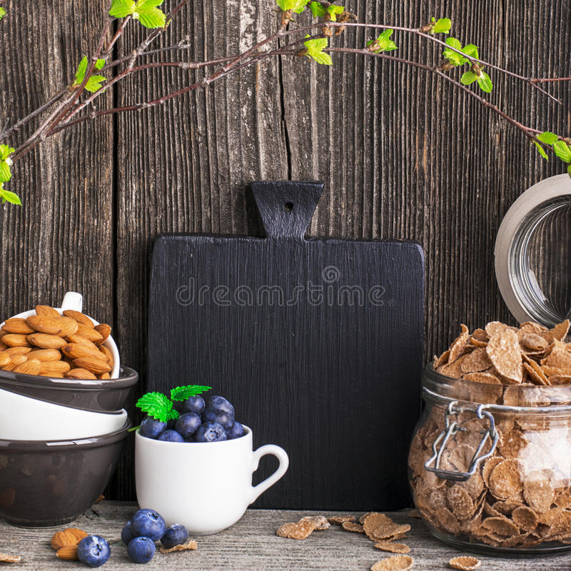 Cozy home kitchen still life with ingredients for a healthy breakfast, blueberries, cereal flakes, nuts in a minimalist. Cozy home kitchen still life with royalty free stock image