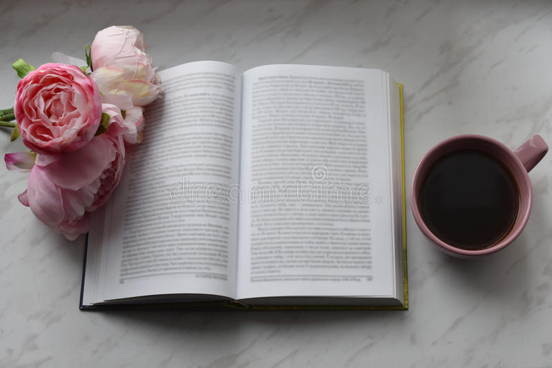Cozy home still life: cup of hot coffee, spring flowers and opened book with warm plaid on windowsill. Springtime royalty free stock photo