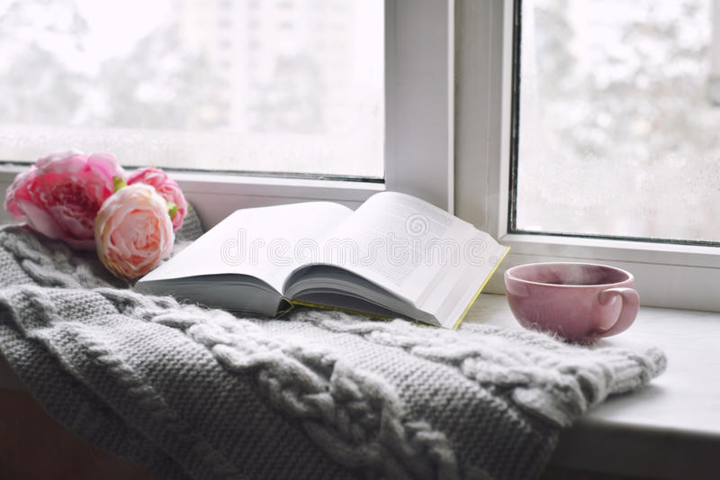 Cozy home still life: cup of hot coffee, spring flowers and opened book with warm plaid on windowsill. Springtime stock image