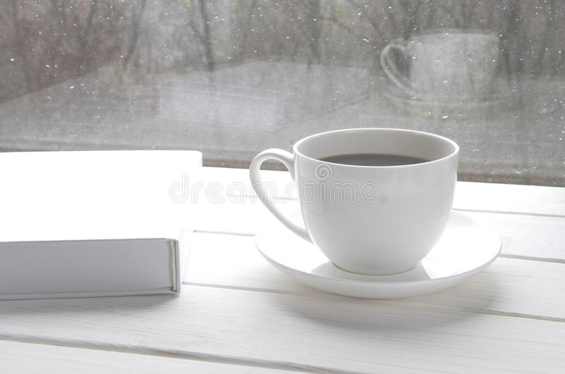 Cozy home still life: white cup of hot coffee and white opened book on windowsill against snow landscape outside stock photos