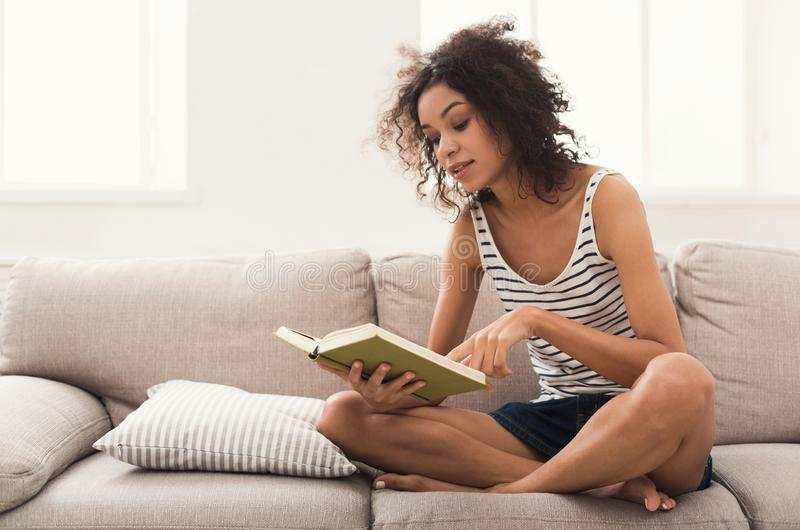 Cozy home. Young thoughtful woman with book royalty free stock photos