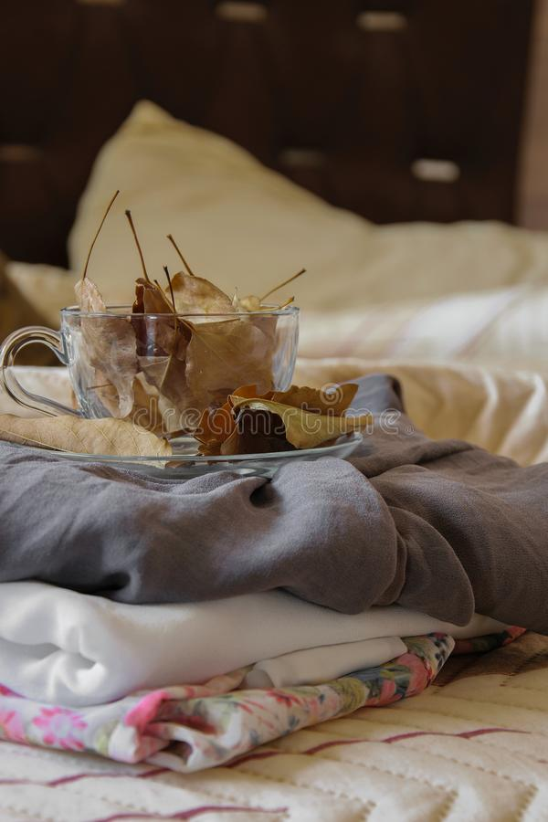 Cozy indoor autumn mood, female clothes folded on the bed with a coffee mug full of autumn leaves stock photos
