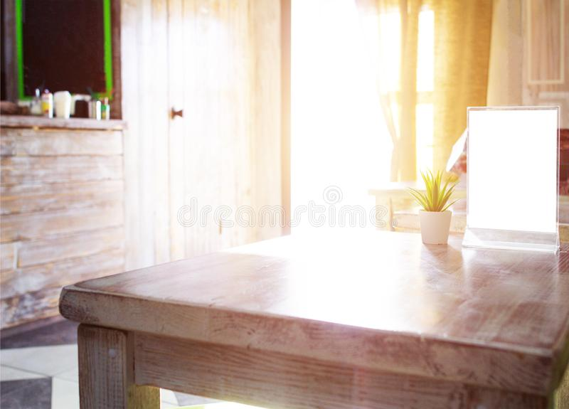 A cozy interior in a coffee shop on a wooden table is a menu the morning sun is shining through the window, copy space, restaurant. A cozy interior in a coffee stock photo
