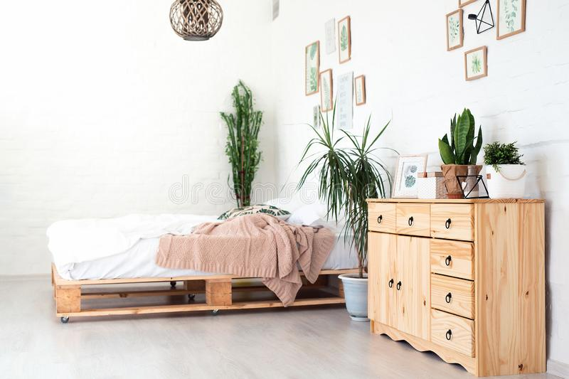 Cozy interior design of modern studio apartment in Scandinavian style. A spacious huge room in light colors with wooden. Bed and stylish expensive luxury stock photo