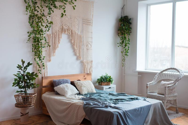 Cozy interior design of modern studio apartment in Scandinavian style. A spacious huge room in light colors with wooden. Bed and stylish expensive luxury royalty free stock photography