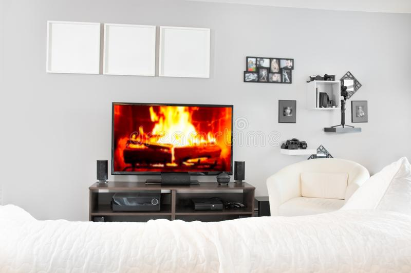 Cozy interior of living room with tv. Fireplace on television screen stock image