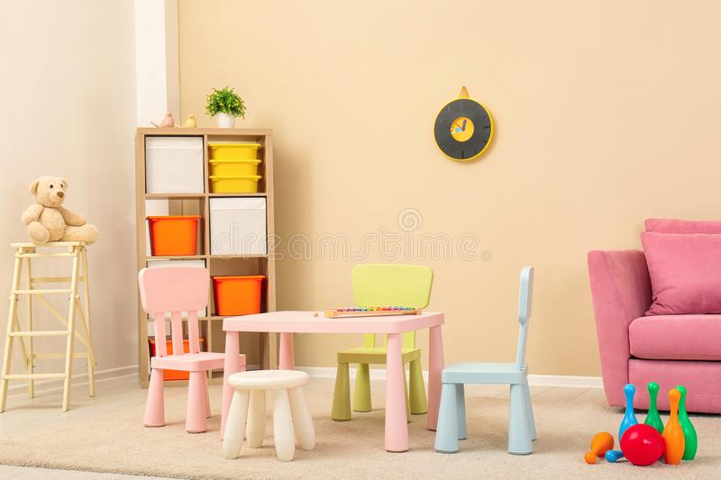 Cozy kids room interior with table, sofa. And shelving unit royalty free stock image
