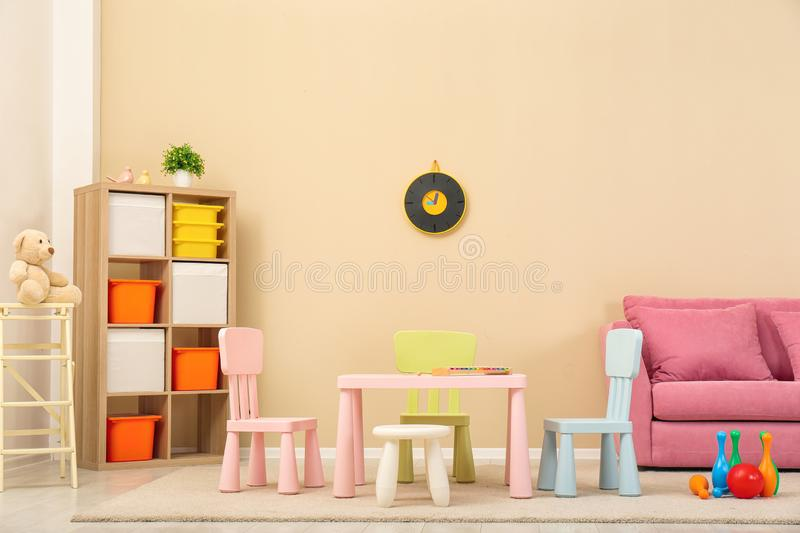 Cozy kids room interior with table, sofa royalty free stock images