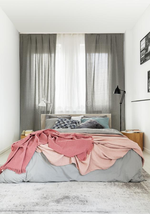Cozy king size bed with grey bedding and warm pastel pink blanket blanket in small bedroom interior.  stock photo