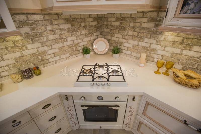 Cozy kitchen, hob. Brick apron in the kitchen. Part of the kitchen with hood royalty free stock image