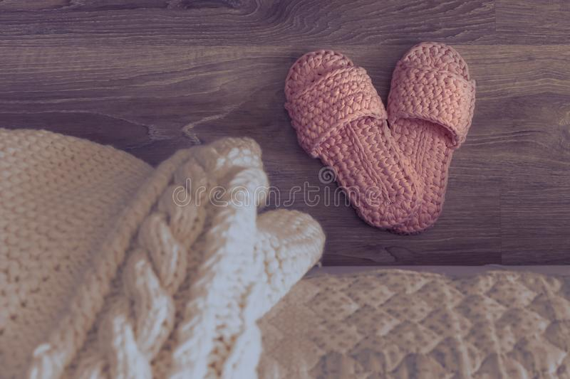 Cozy knitted slippers beside the bed. Night bedroom. White knitted plaid on the bed.  stock photography