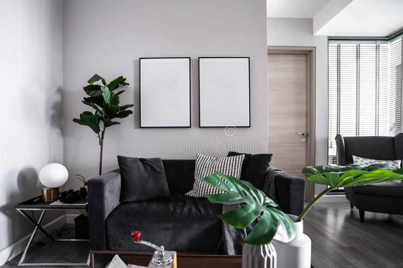 Cozy Living room corner with dark gray velvet fabric sofa , artificial plants and empty picture frame installing on the wall / coz stock photography
