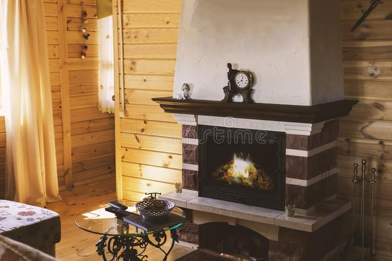 A cozy living room with a fireplace by the sofa and a forged table. Cozy winter concept. Christmas and travel royalty free stock photos