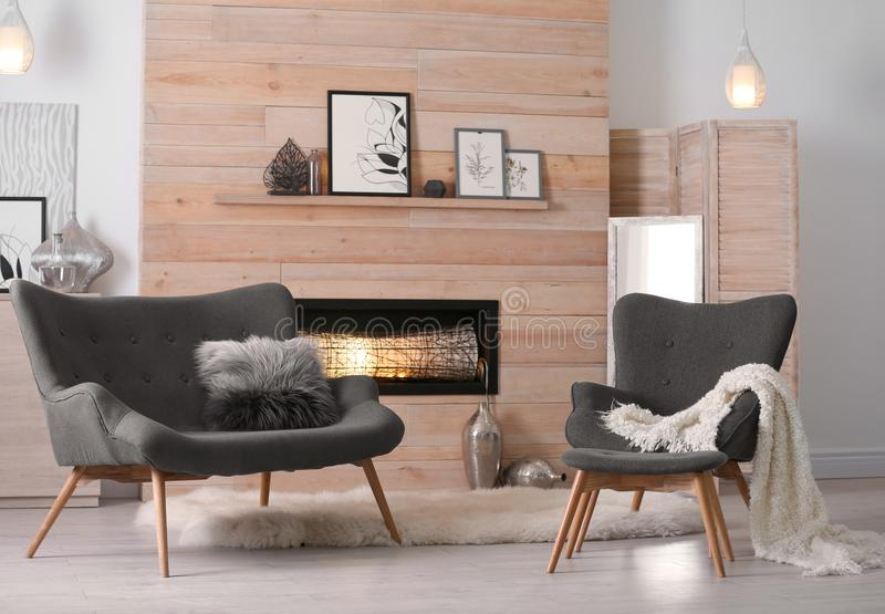 Cozy living room interior with comfortable furniture. And decorative fireplace stock photography