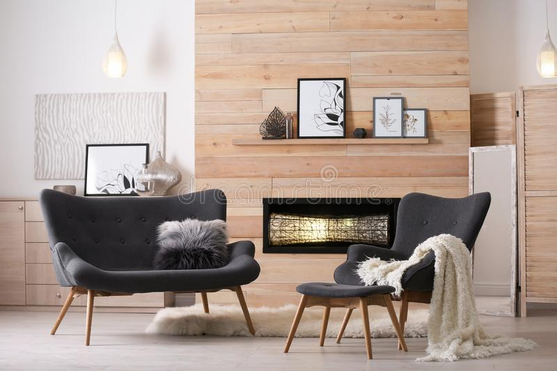 Cozy living room interior with comfortable furniture. And decorative fireplace royalty free stock image