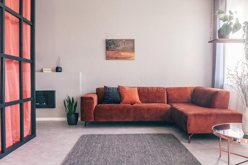 Cozy living room interior with corner sofa with pillows and painting on the wall. Cozy living room interior with sofa with pillows and painting on the wall royalty free stock image