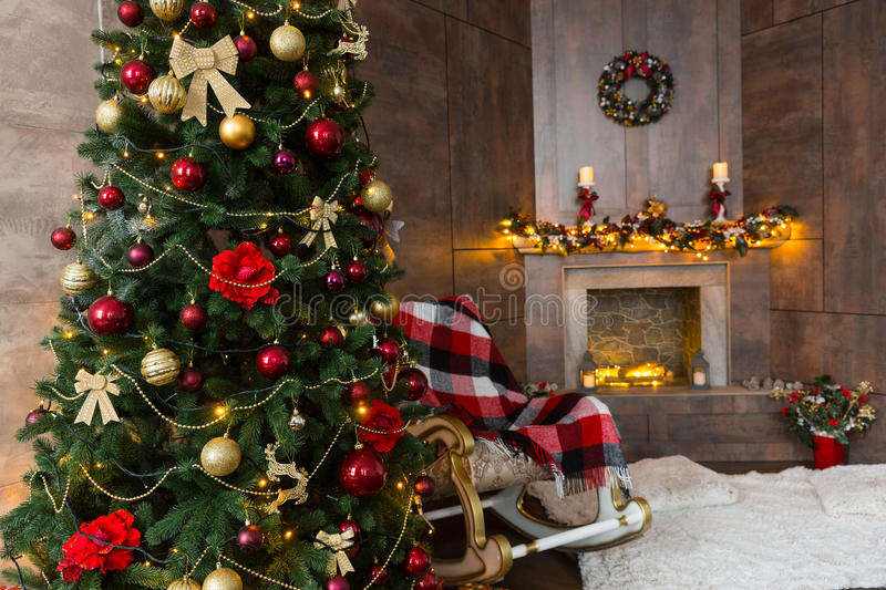 Cozy living room with rocking chair, decorated modern flaming fireplace and large Christmas tree with a lot of presents royalty free stock photography