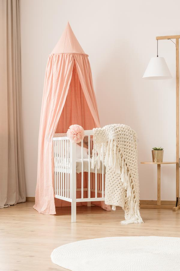 Crib and creative floor lamp. Cozy, modern nursery room interior for a newborn girl with a baby crib by a white wall, dirty pink canopy and a creative floor lamp stock image