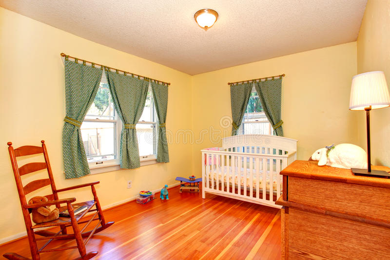 Cozy nursery room with crib and rocking chair. Cozy nursery room in soft ivory with white crib and rocking chair. Room decorated with green curtains stock images