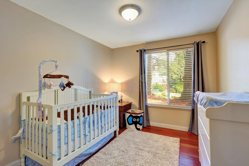 Cozy nursery room with white wooden crib. Cozy nursery room with a crib, carpet and baby changing table. Northwest, USA royalty free stock photos