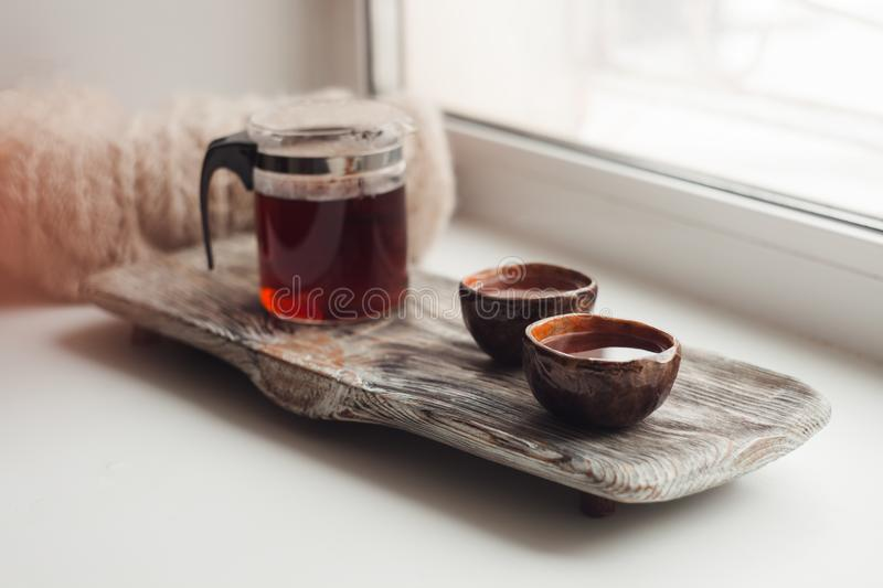 A cozy place to read on the windowsill - Asian tea, a warm scarf, a book, an atmosphere of coziness, inspiration, relaxation stock image