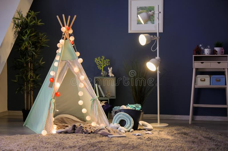 Cozy play tent for kids with glowing garland in room interior royalty free stock photography