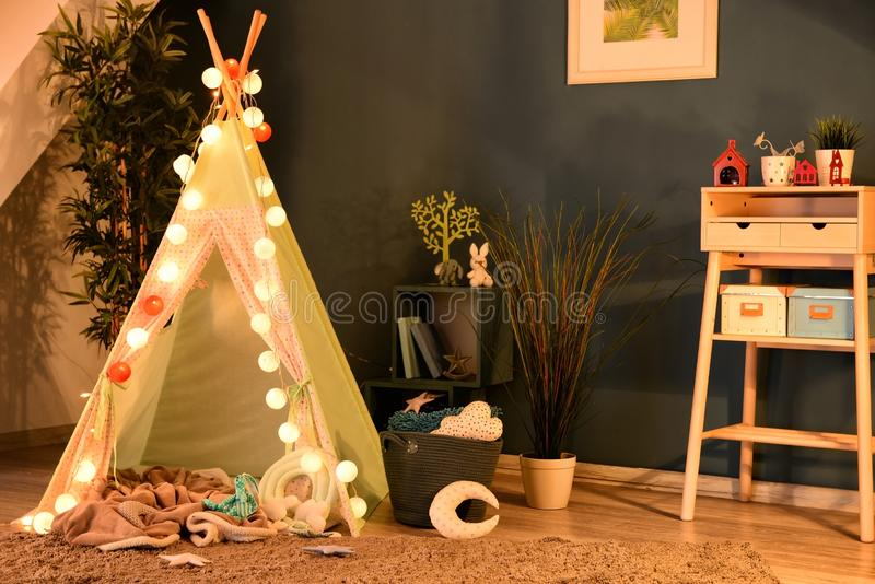 Cozy play tent for kids with glowing garland in room interior stock photos