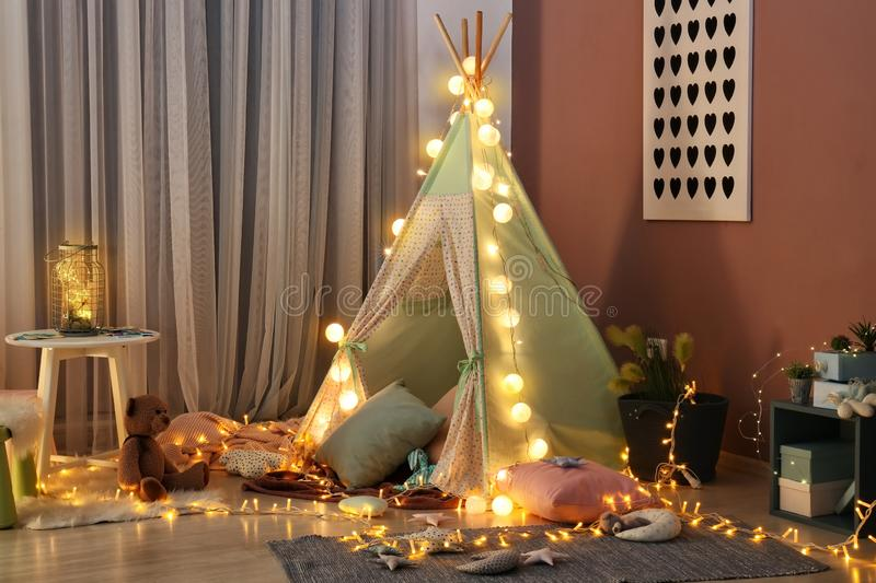 Cozy play tent for kids with glowing garland in room interior stock images